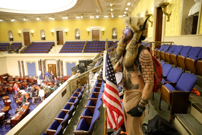 Jacob Anthony Chansley of Phoenix, aka Jake Angeli, yells inside the Senate chamber on Jan. 6, 2021, in Washington, D.C. Chansley entered the building wearing a headdress with horns and carrying a flag attached to a spear.