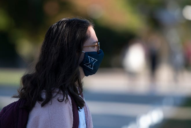 A student walks across campus wearing a Xavier logo mask at Xavier University in Norwood on Friday, Oct. 2, 2020.