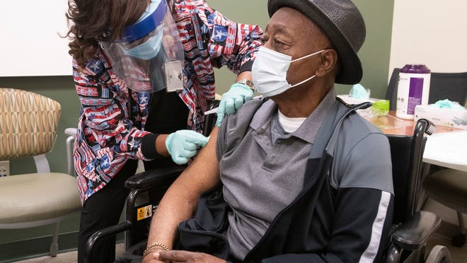 Registered Nurse Linda Hixson prepares to give Joe Knight his first dose of the COVID-19 vaccine on Jan. 12, 2021. Knight, a veteran of the Korean and Vietnam wars, is the first outpatient veteran to receive the new Moderna vaccine at the Joint Ambulatory Care Center in Pensacola, Fla.