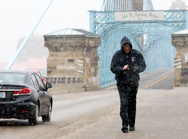 Mark Stickling walks across the Roebling Bridge during a snow storm on Wednesday, Jan. 27, 2021, in Cincinnati.