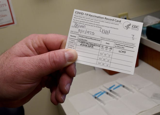 Licking County, Ohio, Health Commissioner Chad Brown shows his vaccination card recording the date of his first dose of the two-dose vaccine. The vaccine is two doses administered 21 or 28 days apart, depending on which company made the vaccine.
