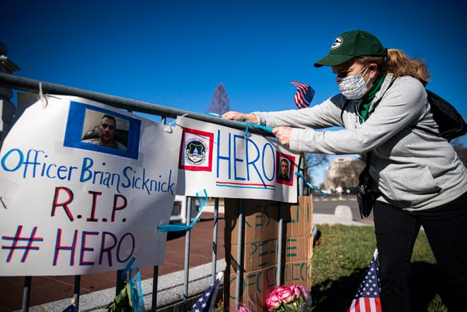 Anne Seymour, a crime victim advocate, creates a makeshift memorial on Jan. 9, 2021, in Washington. for U.S. Capitol Police Officer Brian Sicknick, who was fatally injured when a pro-Trump mob stormed and entered the Capitol Building.
