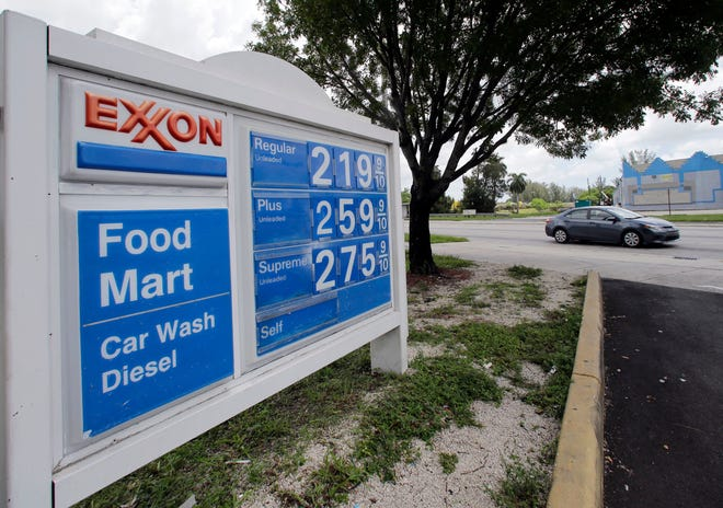 A motorist drives by an Exxon sign displaying gas prices in Opa-locka, Fla., on July 19, 2017.