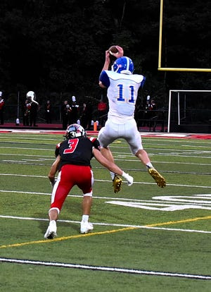 Madeira's Vinnie Englert (11) takes to the air to grab a pass for the Mustangs as Indian Hill's Tre Lopez III applies the defense, Sept. 14, 2018.