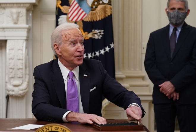 President Joe Biden speaks to the press after signing executive orders as part of the Covid-19 response as Director of NIAID Anthony Fauci looks on.