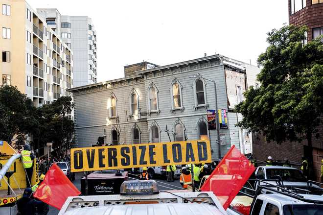 A truck pulls a Victorian home through San Francisco on Sunday, Feb. 21, 2021. The house, built in 1882, was moved to a new location about six blocks away to make room for a condominium development. According to the consultant overseeing the project, the move cost approximately $400,000 and involved removing street lights, parking meters, and utility lines.