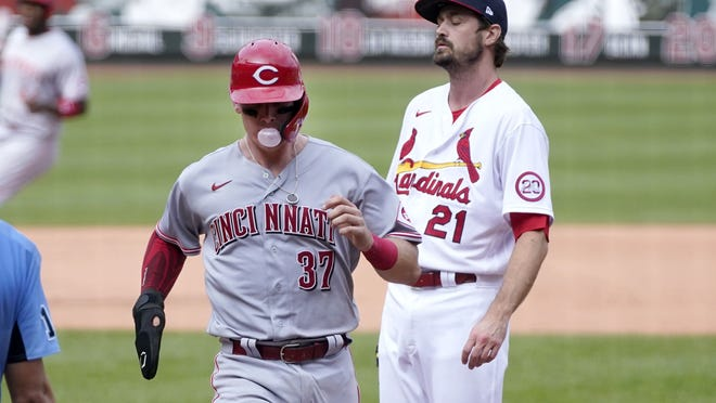Cincinnati Reds' Tyler Stephenson, left, scores on a wild pitch by St. Louis Cardinals relief pitcher Andrew Miller, right, during the seventh inning of a baseball game Sunday, Sept. 13, 2020, in St. Louis. (AP Photo/Jeff Roberson)