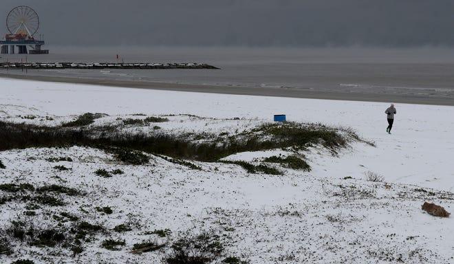 A jogger runs along a snow-covered beach on Monday in Galveston, Texas.