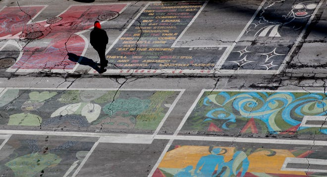 A pedestrian walks across the Black Lives Matter mural on Plum Street in Downtown Cincinnati on Friday, Feb. 19, 2021. Last June, 17 project managers steered a group of 70 artists to design and paint a Black Lives Matter mural in Downtown in front of City Hall. It was unveiled to great fanfare but itÕs never been preserved or protected.