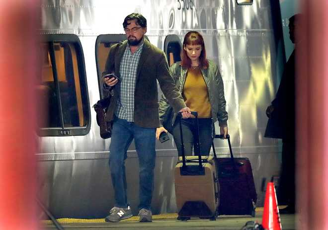 """Actors Leonardo DiCaprio and Jennifer Lawrence walk along the train platform next to an Acela train at South Station during on location filming of """"Don't Look Up"""" at South Station in Boston on Dec. 1, 2020. The film stars Jennifer Lawrence, Leonardo DiCaprio, Meryl Streep, and is directed by Adam McKay."""