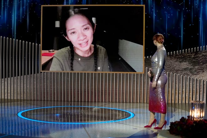 """Chloe Zhao accepts best director for """"Nomadland"""" via video as Bryce Dallas Howard looks on at the 78th annual Golden Globe Awards."""