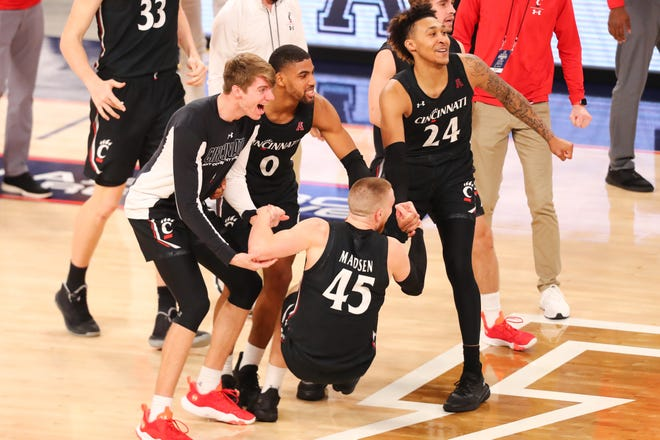 Bearcats guard Mason Madsen (45) is picked up by teammates while celebrating the  victory. UC will be making its  fourth straight appearance in the AAC title game. Last season's event was canceled because of the pandemic.