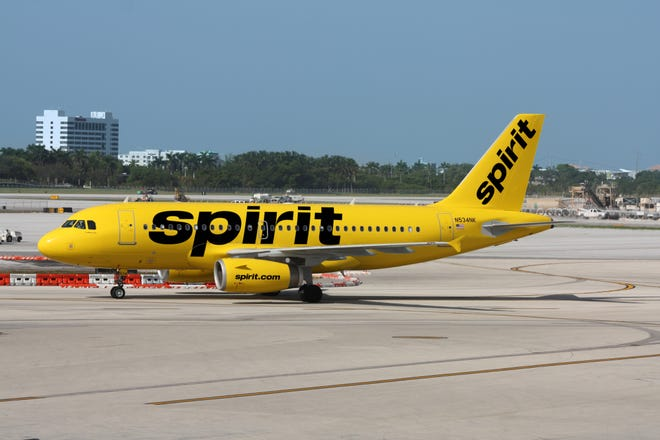A Spirit Airlines jet is shown on a taxiway. The airline is an ultra-low-fare carrier.