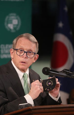 Gov. Mike DeWine removes his mask to take a question during a press conference Tuesday at Cleveland State University's Wolstein Center. DeWine toured the FEMA mass COVID-19 vaccination site at the Wolstein Center prior to the press conference.