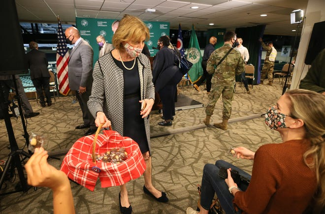 Ohio First Lady Fran DeWine passes out her Fran's Buckeye Brownies after Gov. Mike DeWine's press conference Tuesday at Cleveland State University's Wolstein Center in Cleveland. DeWine toured the FEMA mass COVID-19 vaccination site at the Wolstein Center prior to the press conference.