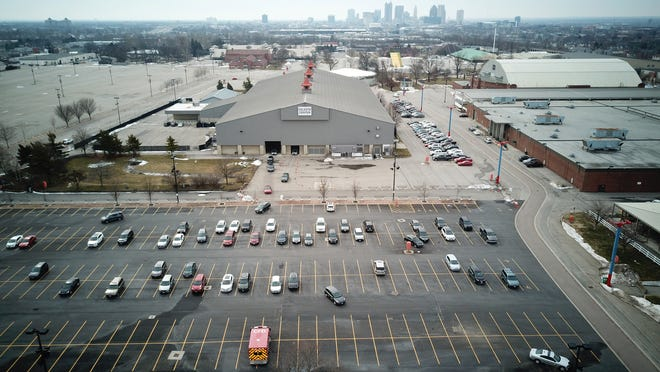 A parking lot is partially filled with people who have been instructed to wait inside their cars for 15 minutes after receiving a COVID-19 vaccine at the drive-through Celeste Center at the Ohio Expo Center, 717 E. 17th Ave. in Columbus on Friday, Feb. 26, 2021. They enter through doors on the other side of the building, stay in their cars and get the shot, then exit through the visible doors of the Celeste Center, which is the gray building in the center of the picture. Columbus Fire Department paramedics monitor the parking lot for people having bad reactions to the vaccine. Downtown Columbus is visible at the top of the image.  For more infomation, call Columbus Public Health's COVID-19 hotline at 614-645-1519.