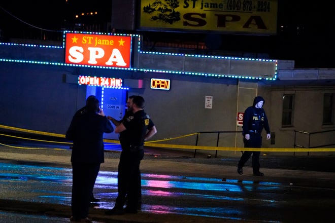 Law enforcement officials confer outside a massage parlor following a shooting on Tuesday, March 16, 2021, in Atlanta. Shootings at two massage parlors in Atlanta and one in the suburbs have left multiple people dead, many of them women of Asian descent, authorities said Tuesday.