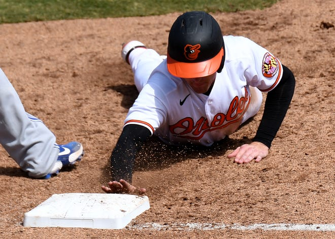 Baltimore prospect Tyler Nevin slides back to first base during a spring training game.