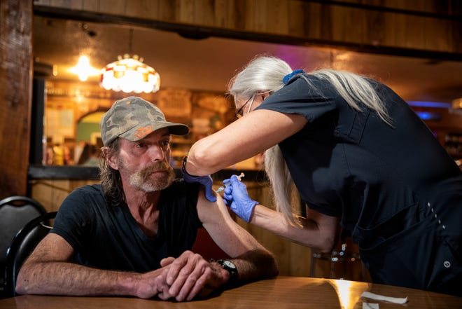 Kim Neace, a nurse practitioner, administers the Johnson & Johnson COVID-19 vaccine to Wilbur Gray at the Long Branch Tavern in Laurel, Ind., on June 7. Gray had wanted to get the vaccine for months, but did not have a car and could not travel to a clinic or pharmacy.