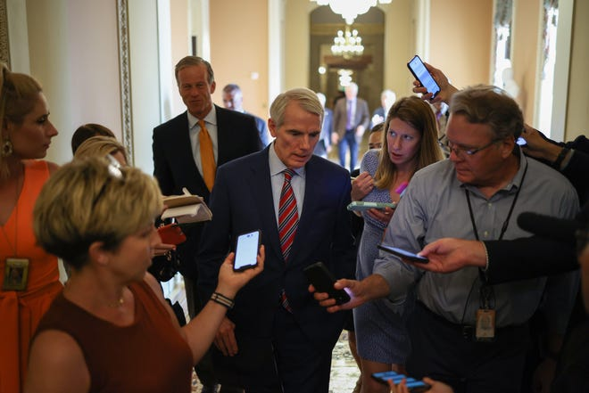 Sen. Rob Portman, R-Ohio, center, says details need to be worked out in the infrastructure bill.
